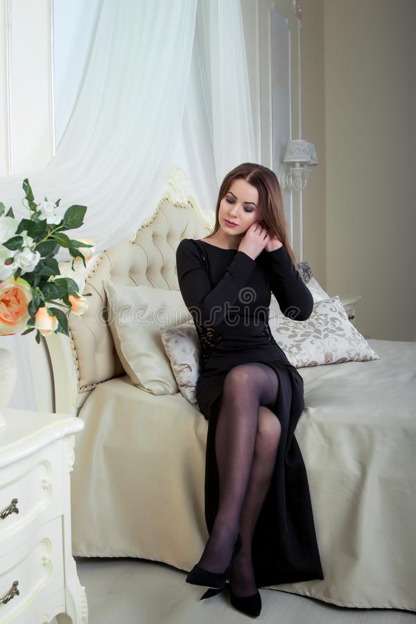 Portrait of beautiful young brunette woman sitting in bedroom, putting earring on royalty free stock photo