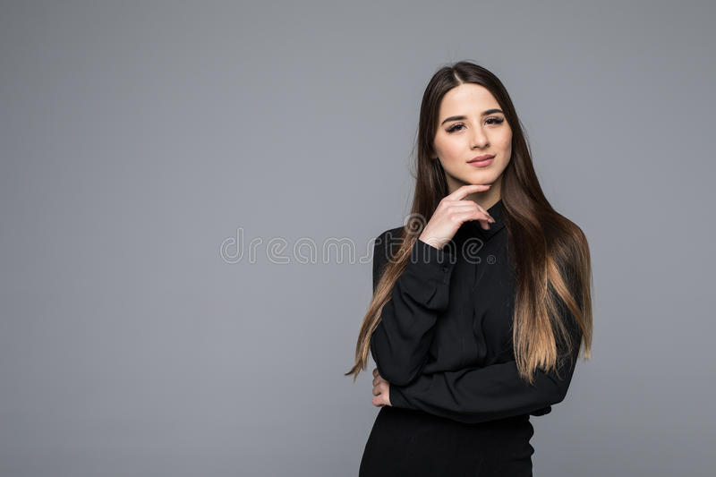 Portrait of a beautiful young business woman against grey background royalty free stock image
