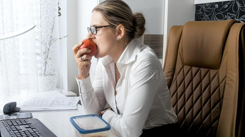 Portrait of beautiful young businesswoman having lunch on working place royalty free stock images