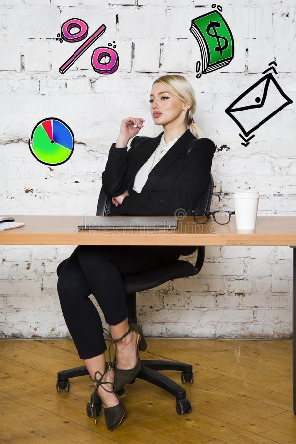 Portrait of a beautiful young businesswoman wearing a white shirt and black suit and thinking. Business concept. stock photography