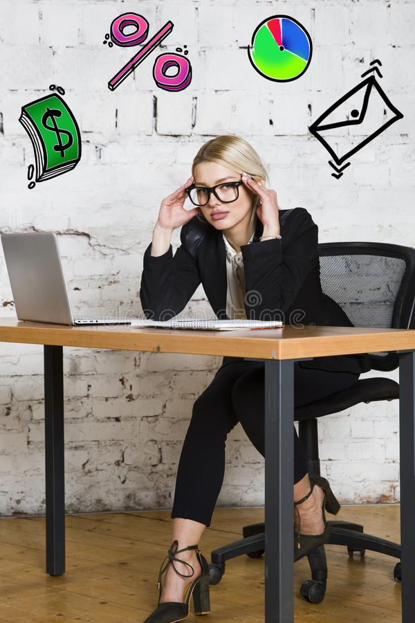 Portrait of a beautiful young businesswoman wearing a white shirt and black suit and thinking. Business concept. Portrait of a beautiful young businesswoman royalty free stock image