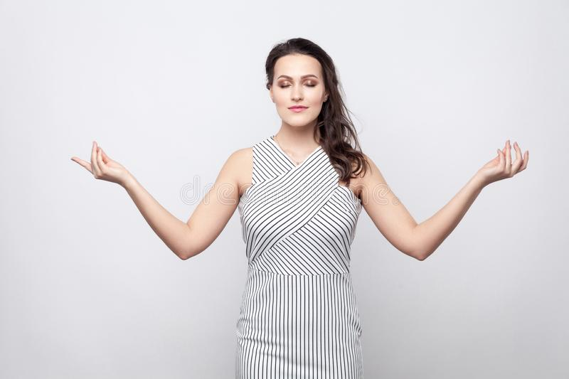 Portrait of beautiful young calm brunette woman with makeup and striped dress standing with closed eyes and crossed hands in yoga royalty free stock photography