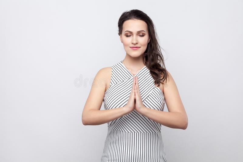 Portrait of beautiful young calm brunette woman with makeup and striped dress standing with closed eyes and palm hand in yoga pose stock photo
