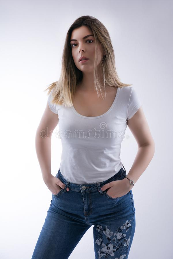 Portrait of beautiful young caucasian student girl with blonde hair in white t shirt and blue jeans royalty free stock photography