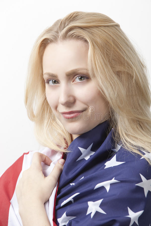 Portrait of beautiful young Caucasian woman wrapped in American flag against white background stock photo