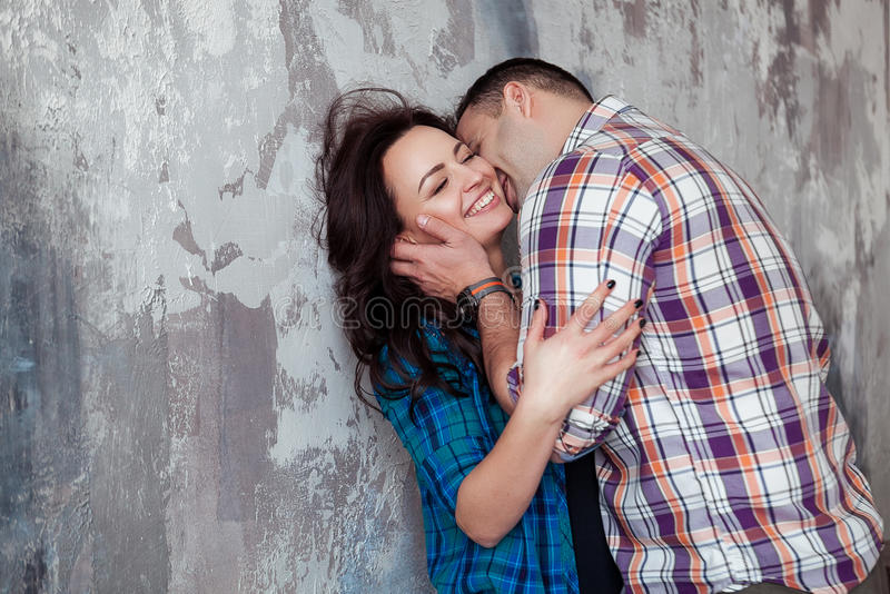 Portrait of beautiful young couple in casual clothes hugging and smiling, standing against gray wall royalty free stock image