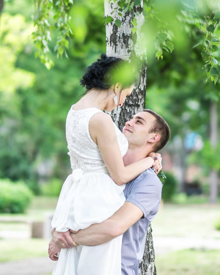 Portrait of beautiful young couple female bride and male bridegroom hugging and looking at each other in summer park. Man husband stock photos