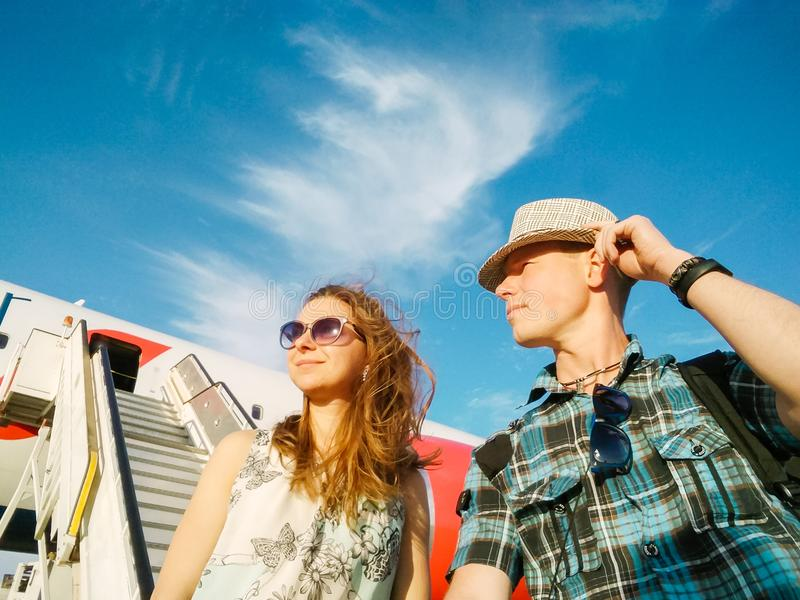 Portrait of beautiful young couple near the plane against the blue sky on summer day. Tourism and travelling concept, bottom view. royalty free stock photos