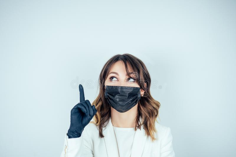 Portrait of a beautiful and young doctor woman in white medical gown , black rubber gloves and black mask on face finger. Pointing up stock image