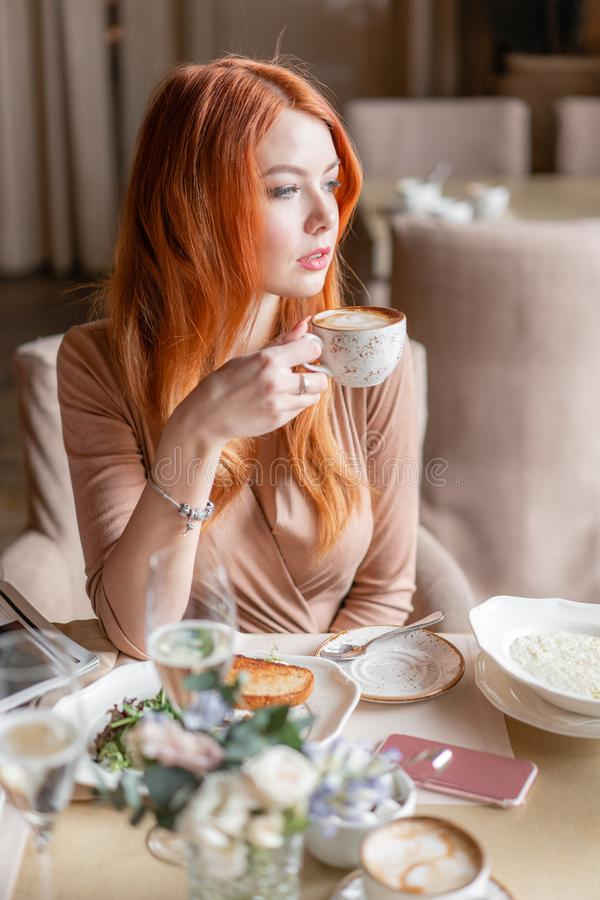 Nice redhead woman eat breakfast in cafe. Portrait of young charming female drinking coffee and toasted sandwich in royalty free stock photos