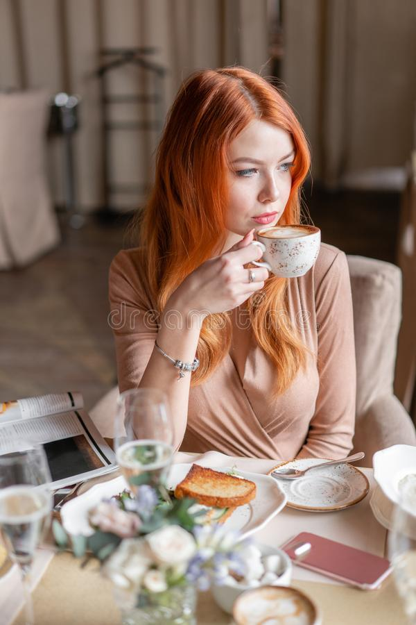 Nice redhead woman eat breakfast in cafe. Portrait of young charming female drinking coffee and toasted sandwich in royalty free stock image
