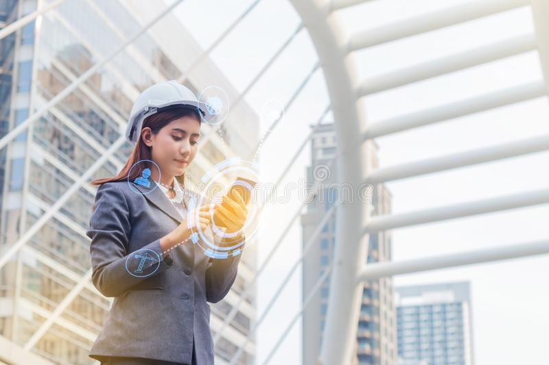 Portrait of beautiful young engineer woman wear a white safety helmet. She are smile and talking on smartphone with commitment to. Success with building royalty free stock photography