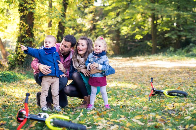 Beautiful young family with small twins on a walk in autumn forest, resting. royalty free stock photos