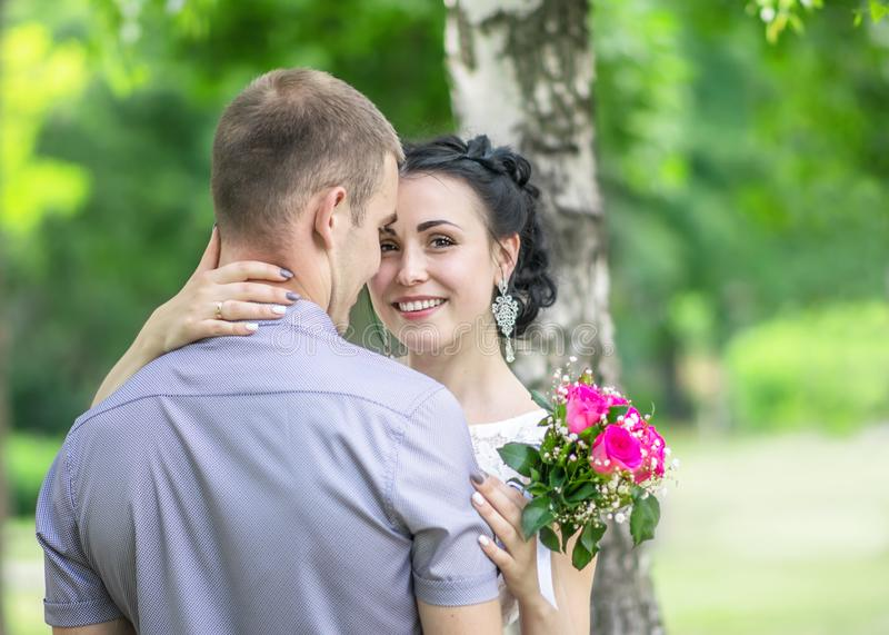 Portrait of a beautiful young female bride with small wedding pink flower roses bouquet smiling, gently hugging bridegroom neck an stock photos