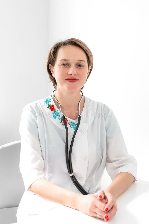 Portrait of a beautiful young female doctor professional therapist in the workplace royalty free stock image