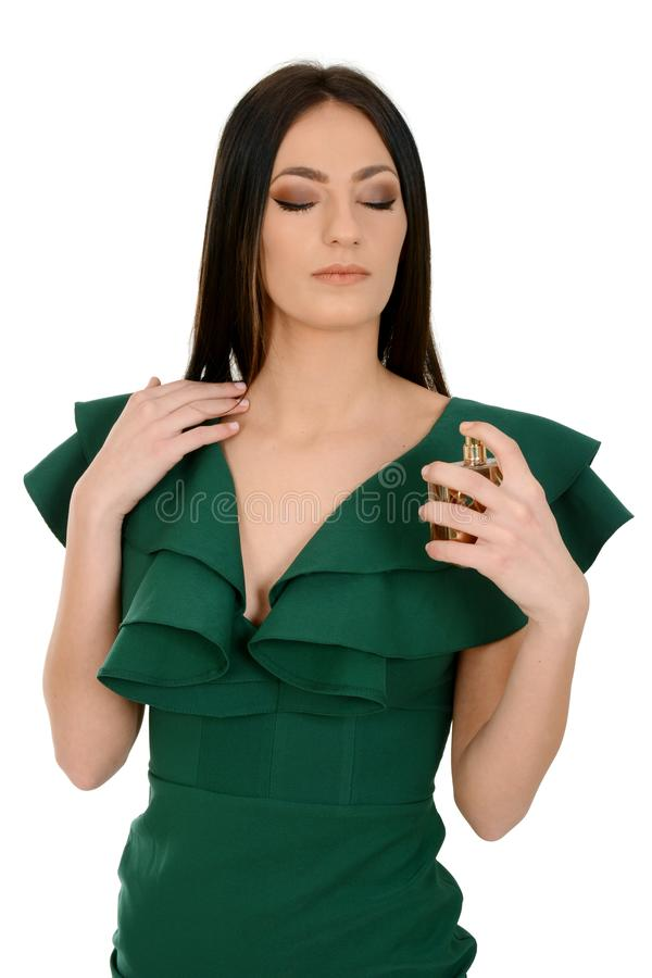 Portrait of a beautiful young female in green dress applying a perfume royalty free stock photo
