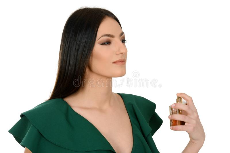 Portrait of a beautiful young female in green dress applying a perfume royalty free stock image