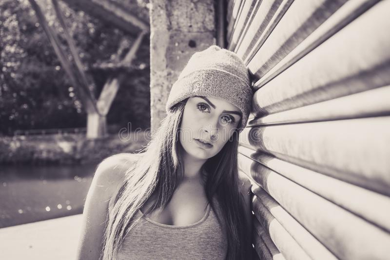 Portrait of beautiful young female model, leaning against a garage door. stock photos