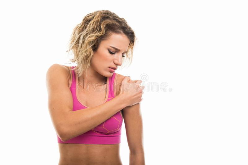 Portrait of beautiful young fit girl holding shoulder like hurting stock image