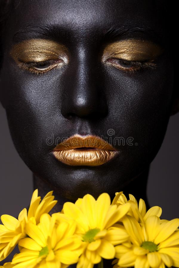 Portrait of a beautiful young girl and creative make-up. With golden lipstick and yellow flowers royalty free stock image