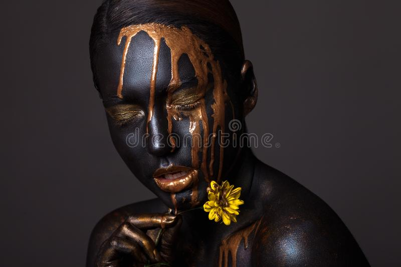 Portrait of a beautiful young girl and creative make-up. With golden lipstick and yellow flowers stock images