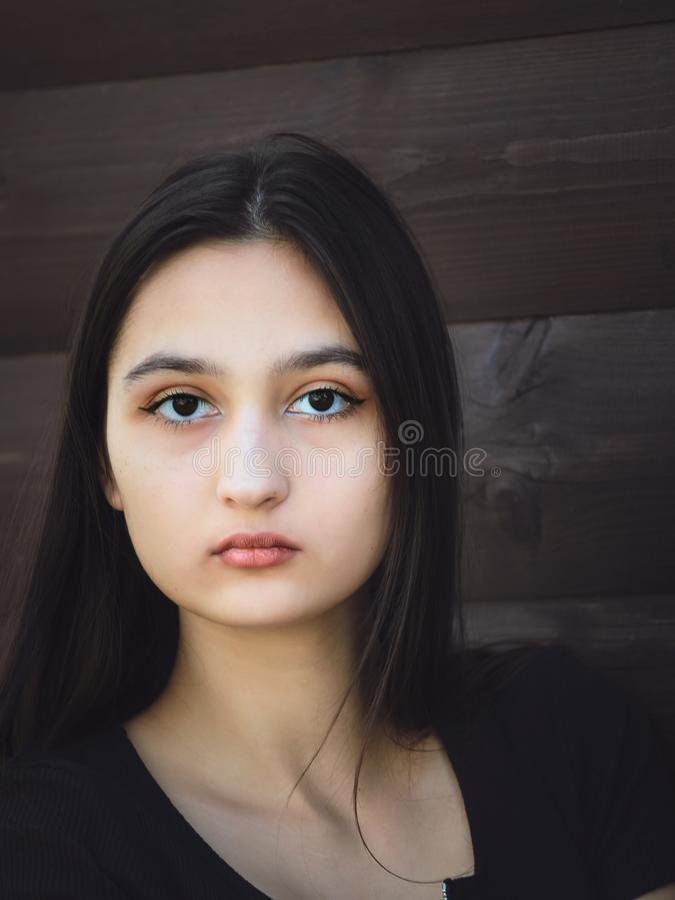 Portrait of a beautiful young girl with dark long hair and black eyes royalty free stock photos