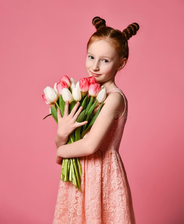 Portrait of a beautiful young girl in dress holding big bouquet of irises and tulips isolated over pink background stock photography