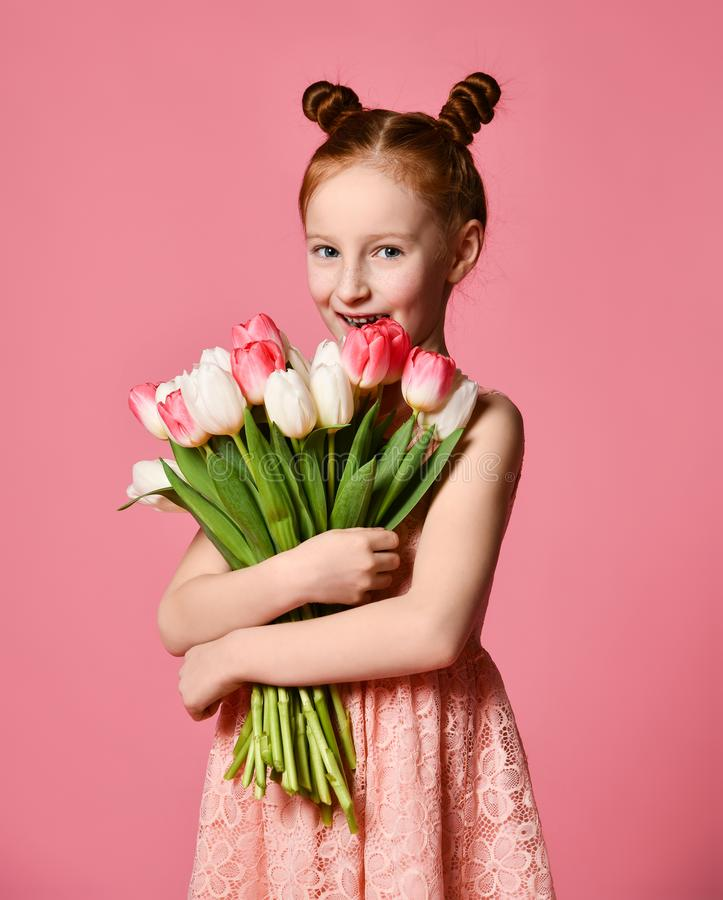 Portrait of a beautiful young girl in dress holding big bouquet of irises and tulips isolated over pink background stock images