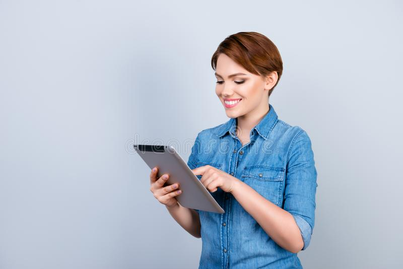 Portrait of beautiful young girl in jeans shirt holding digital stock photography
