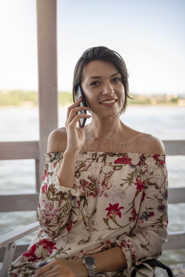 Portrait of beautiful smiling young girl with phone on sunny day stock photos