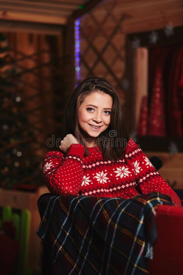 Portrait of a beautiful young girl in a red Christmas sweater. Christmas background behind. holiday concept royalty free stock image