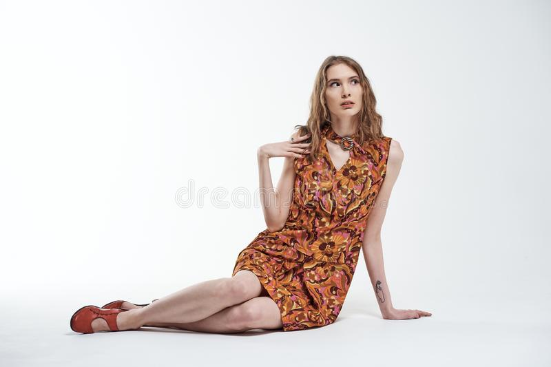 Portrait of a beautiful young girl sits on the white floor and looks up in surprise royalty free stock image