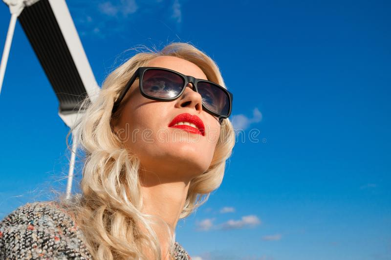 Portrait of a beautiful young girl in sunglasses looking afar, against the blue sky royalty free stock photo