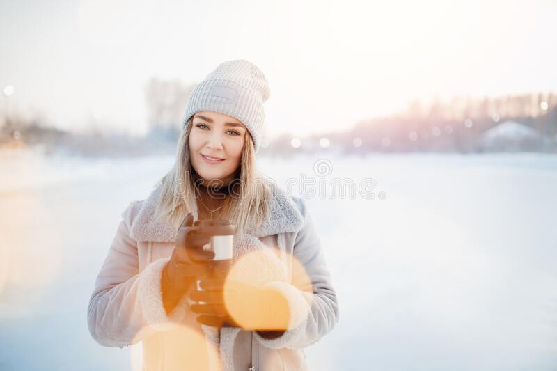 Portrait beautiful young girl in warm clothes and hat in winter holds thermos mug with hot tea, bokeh blurred background.  stock images
