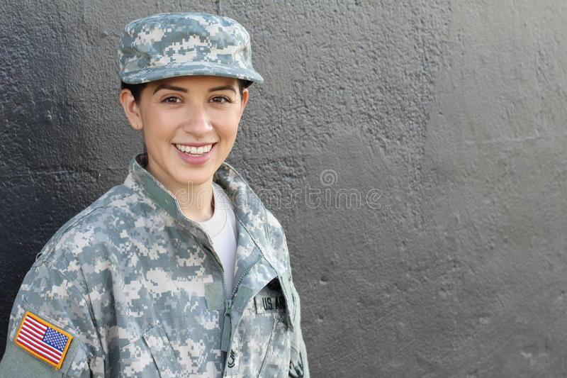 Portrait of beautiful young girl wearing green military style jacket and hat on gray stock photos