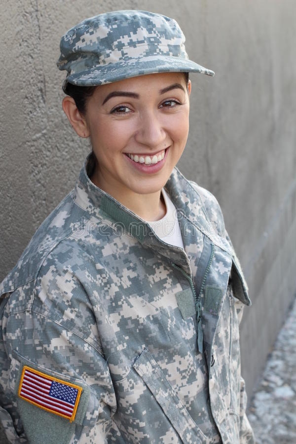 Portrait of beautiful young girl wearing green military style jacket and hat on gray stock image