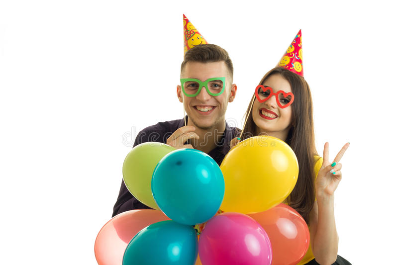 Portrait of a beautiful young happy couples in glasses and balloons in hands royalty free stock images