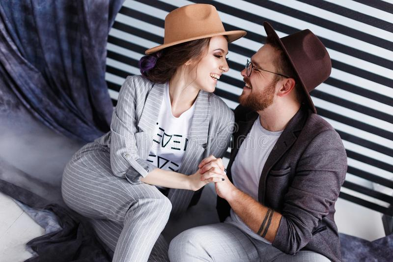 Portrait of a beautiful young happy smiling couple. Modern hipster man and woman in studio with copyspace stock photo