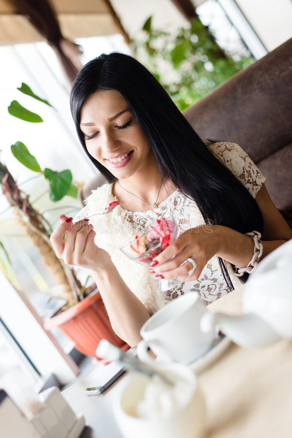 Portrait of beautiful young happy smiling woman having fun eating ice cream in coffee shop or restaurant stock photography