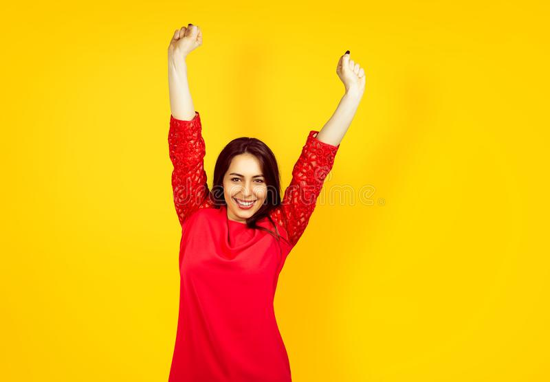 Beautiful young happy woman on a yellow background royalty free stock image
