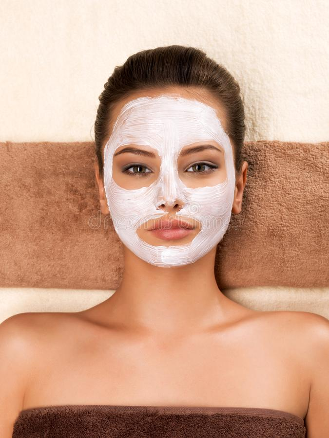 Young woman with mask on her face relaxing in the spa salon. Portrait of beautiful young healthy woman with mask on her face relaxing in the spa salon. Beauty royalty free stock photography