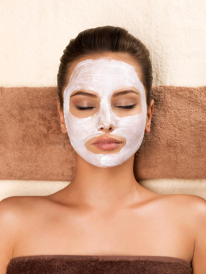 Young woman with mask on her face relaxing in the spa salon. Portrait of beautiful young healthy woman with mask on her face relaxing in the spa salon. Beauty stock photos