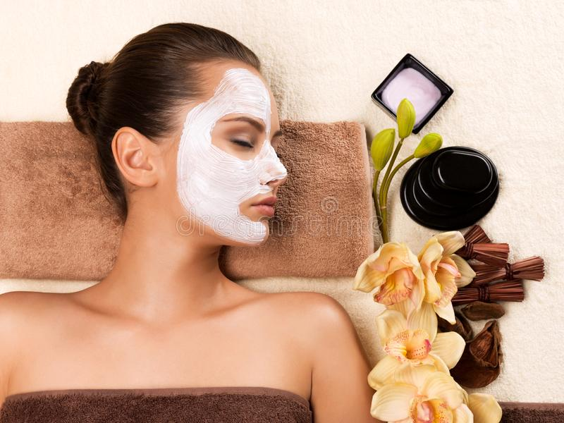 Young woman with mask on her face relaxing in the spa salon. Portrait of beautiful young healthy woman with mask on her face relaxing in the spa salon. Beauty royalty free stock image