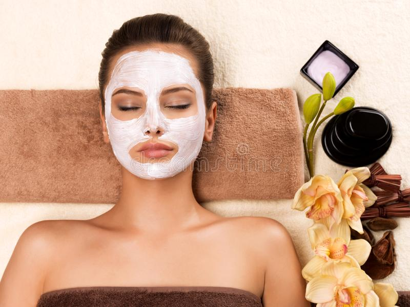 Young woman with mask on her face relaxing in the spa salon. Portrait of beautiful young healthy woman with mask on her face relaxing in the spa salon. Beauty stock photography