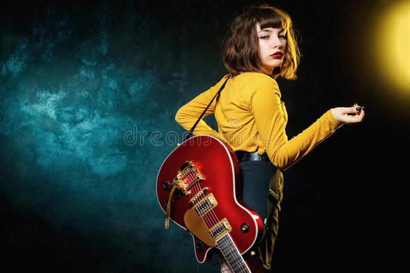 Portrait of beautiful young hipster woman with curly hair with red guitar in neon lights. Rock musician is playing. Electrical guitar. 90s style concept stock image