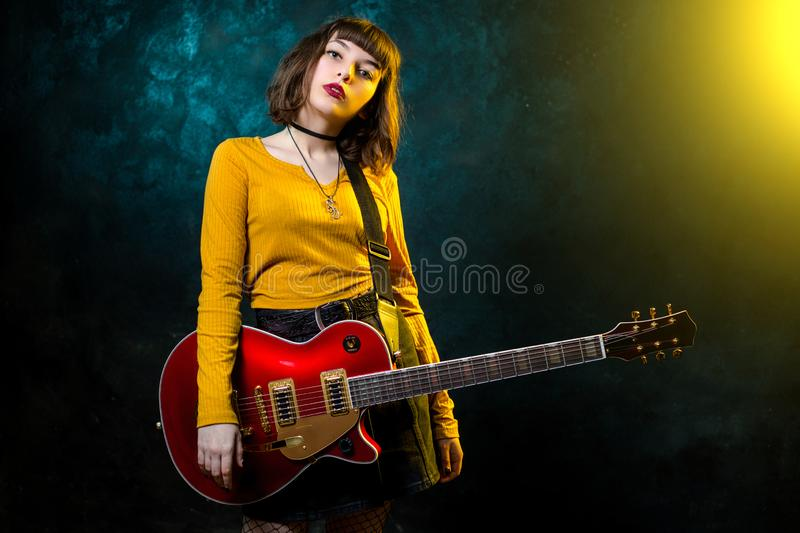 Portrait of beautiful young hipster woman with curly hair with red guitar in neon lights. Rock musician is playing royalty free stock photos