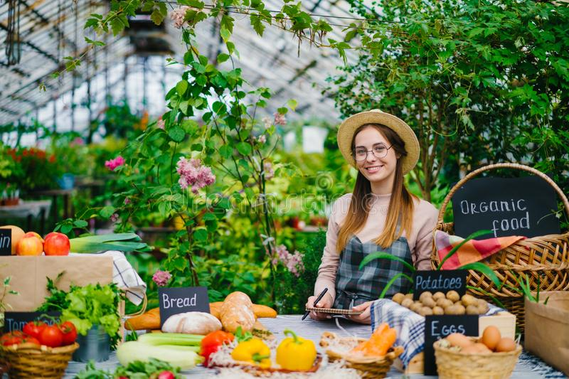 Portrait of beautiful young lady farmer selling organic food in farm market. Smiling looking at camera standing indoors in spacious greenhouse. People and royalty free stock image
