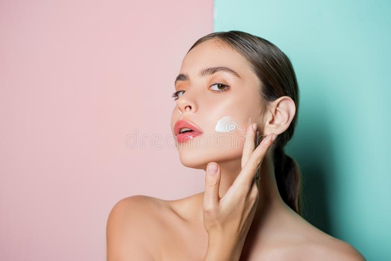 Portrait of beautiful young lady touching cheek with hand applying face cream. Selfcare routine and healthy mood. Pure stock photography