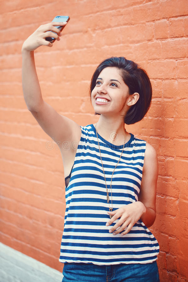 Portrait of beautiful young latin hispanic girl woman outside making selfie photo with cell phone stock photos