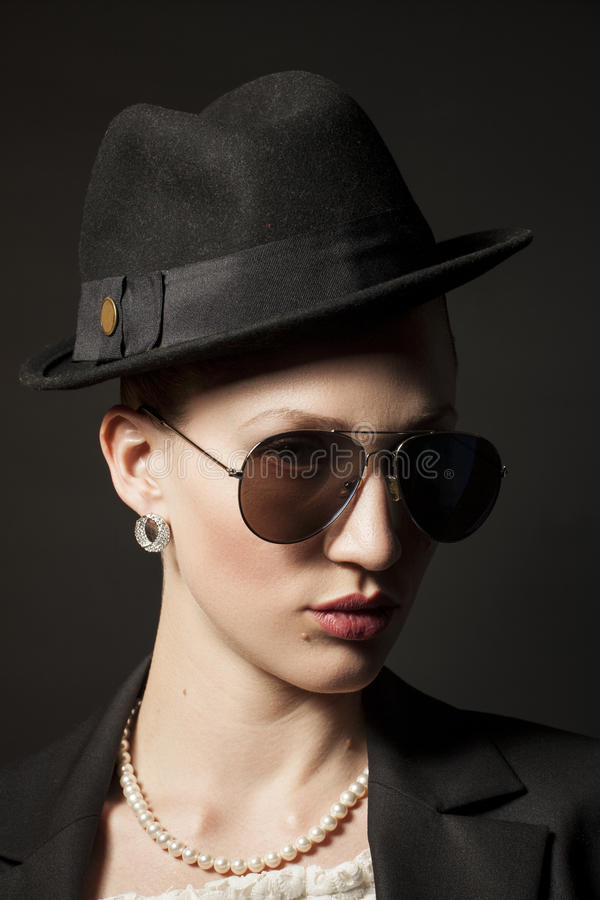 Portrait of a beautiful young model in black hat with sunglasses royalty free stock photos